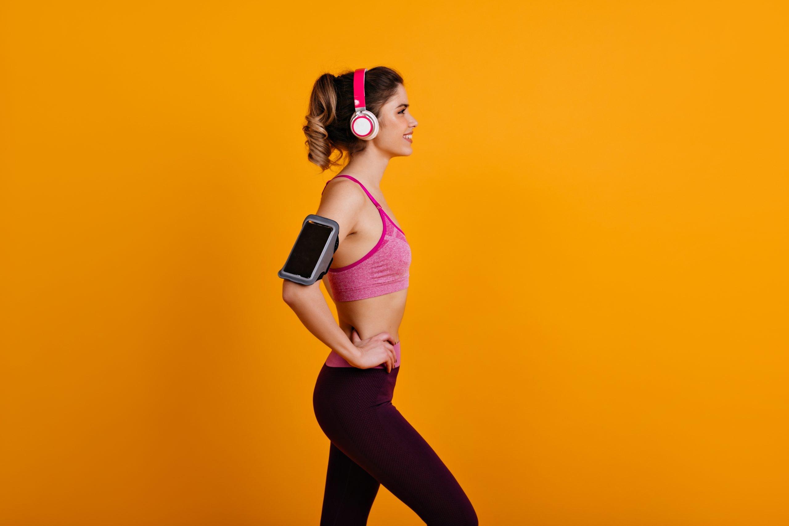 Shapely lady doing cardio. Portrait of fitness girl isolated on orange background.